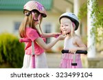 little girl helping her sister... | Shutterstock . vector #323499104