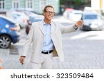 Small photo of Give me a lift. Pleasant upbeat handsome adult man holding his bag and keeping hand up while standing in the street