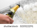 the waiter pours champagne into ... | Shutterstock . vector #323522291