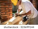 Senior man finishing wooden beam with sander - stock photo