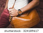 Small photo of young guy with a beard and mustache and white T-shirt posing on the street vintage man, fashion men, hipster street casual leather bag and hours against the background of a brick wall