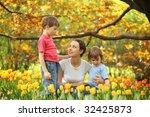 Mother With Children In Garden...