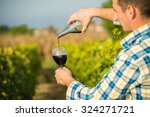 two hands pouring red wine in... | Shutterstock . vector #324271721