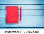 Red Notebook With Pen On Blue...