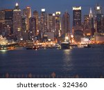 This is a section of the New York City skyline at night. - stock photo