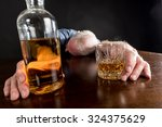 Small photo of Drunk man slumped on table after alcohol abuse