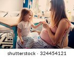 pregnant mother playing with... | Shutterstock . vector #324454121