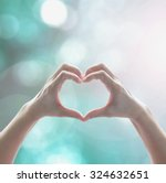 Healthy human hand in single heart shape showing love friendship on blurred abstract cool blue green sky color bokeh background: Global eco environment CSR bio natural resource concept/ campaign/ idea