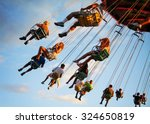 a swinging fair ride at dusk... | Shutterstock . vector #324650819