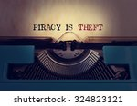 Small photo of closeup of a blue retro typewriter and the text piracy is theft written with it in a yellowish foil