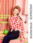 Small photo of Pretty pin-up girl teenager smarten up on a pink kitchen. Beauty, youth fashion. Pin-up style.