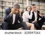 Small photo of Gossip colleagues in front of their office sitting on stairs, depressed businessman portrait and gossip out of focus in background. Reason is racism. Shallow depth of field.