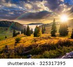 hillside with coniferous forest among the fog on a meadow under the rainbow  in mountains of Romania in evening light - stock photo