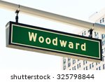 """Street sign for Woodward Avenue, a main thoroughfare in the City of Detroit, Michigan.  This is where the annual """"Dream Cruise"""" is held.  There is a generic office building in the background."""