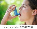 Small photo of Portrait of a girl using asthma inhaler
