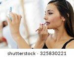 beautiful woman applying... | Shutterstock . vector #325830221