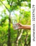 woman hand holding water bottle ... | Shutterstock . vector #325974179