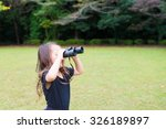 girl playing with binoculars | Shutterstock . vector #326189897
