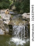 Small photo of CHIANG MAI, THAILAND - JANUARY 16, 2014: Agile gibbon is sitting over the waterfall. The Chiang Mai zoo