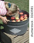 A Young Girl Bobbing For Apples