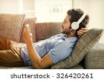 man on couch watches a movie on ... | Shutterstock . vector #326420261