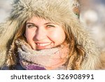 Girl smiling, looking at the camera. Winter snow on the background. Girl in a fur hat and scarf. It