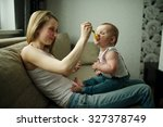 young mother feeding baby with... | Shutterstock . vector #327378749