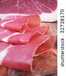 Closeup of sliced ham, typical italian prosciutto on wood trencher - stock photo