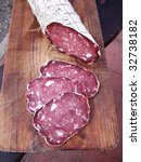Italian typical salami with slices on wood trencher - stock photo
