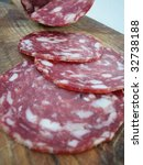 Closeup of italian typical salami slices on wood trencher - stock photo