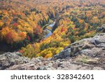 Trees in full autumn color and a small river viewed from rocky overlook in the Porcupine Mountains of Michigan