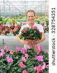 Small photo of Best service. Upbeat agreeable content handsome florist holding flower in a pot and expressing gladness while smiling