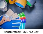 Small photo of Paint containers color sampler safety gloves paintbrushes adhesive tape.
