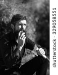 Small photo of One strong male logger of young man with long lush beard and moustache in shirt holding wooden axe sitting in forest smoking cigarette outdoor on natural background black and white, vertical picture