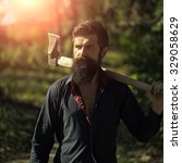 Small photo of One handsome strong stylish male logger of young man with long lush black beard and moustache in shirt holding wooden axe walking in forest outdoor on natural background, square picture
