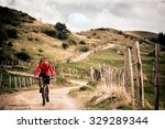 Mountain biker riding on bike in summer mountains landscape. Man cycling MTB on rural country road. Sport fitness motivation and inspiration. - stock photo
