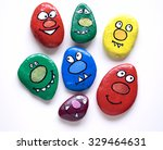 Seven smiling faces of monsters. Funny painted acrylic pebbles. Daylight, on a white background with shadows. The correct orientation of individuals.