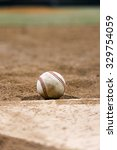 Baseball on top of homeplate with dirt and pitcher's mound in background - stock photo