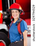 Small photo of Portrait of smiling firewoman wearing red helmet against firetruck at station