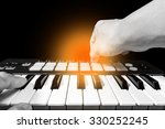 Small photo of male musician, pianist hands playing synthesizer & amber light
