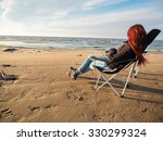 Woman Sitting On Deckchair At...