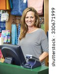 Small photo of Female Cashier At Sales Desk