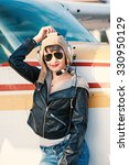 Small photo of Young woman airplane pilot portrait on landing strip. Filtered image.