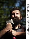 Small photo of Portrait of one handsome strong stylish male logger of young serious man with long lush black beard and moustache in shirt holding wooden axe standing sunny day outdoor on natural background, vertical