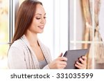 Small photo of Good news. Beautiful young girl checks something on her tablet notepad and smiles absent-mindedly.