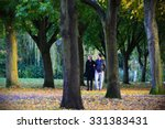 Small photo of TROWBRIDGE - OCT 25: A couple walk through a public park on Oct 25, 2015 in Trowbridge, UK. The UK experiencing an 'Indian Summer' with above average temperatures and stunning fall colours.
