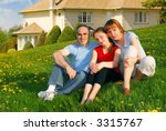 Portrait of a happy family of three on the lawn on front of their house - stock photo