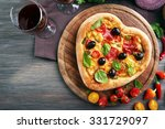 Heart shaped pizza served on wooden table, closeup