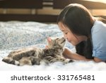 Stock photo beautiful asian girl kissing american shorthair cat on the bed 331765481