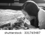 Stock photo beautiful asian girl kissing american shorthair cat on the bed 331765487